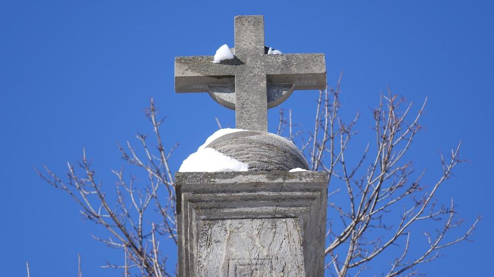 Une croix en pierre sur fond de ciel bleu