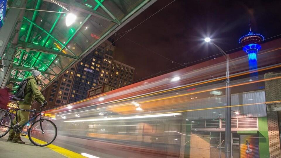 Deux hommes attendent l'arrivée du train léger sur rail à une station du centre-ville de Calgary. La station est proche de la tour de Calgary.