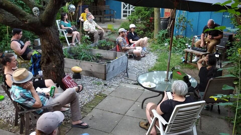 des amis écoutent un clarinettiste dans un jardin
