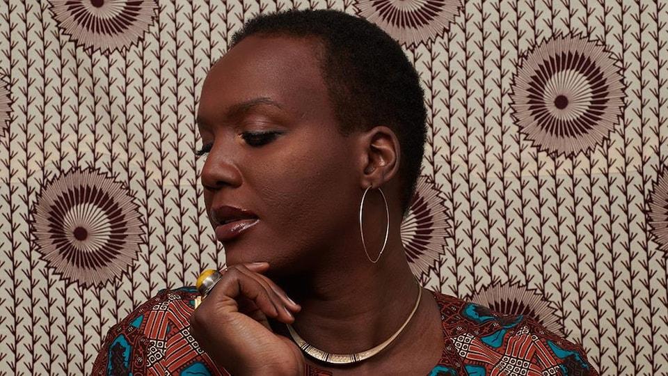 Alicia, de profil. les yeux baissés, devant un fond aux motifs africains.