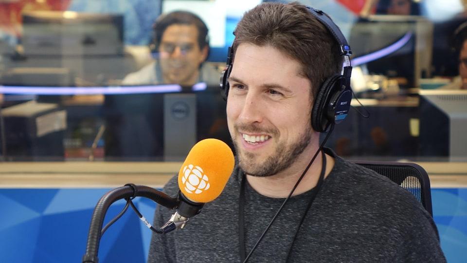 David Goudreault derrière un micro dans un studio radio de Radio-Canada.