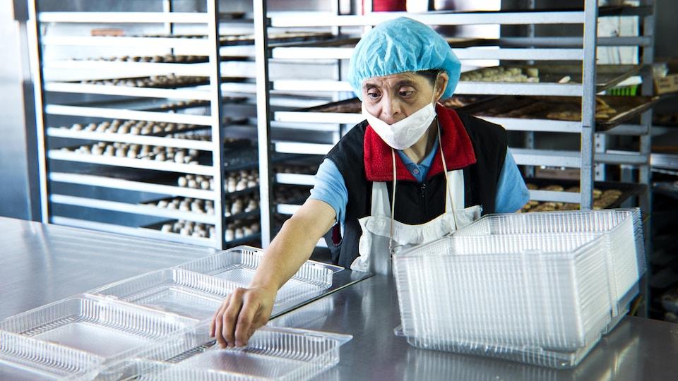 Une femme, avec un bonnet sur la tête pour retenir ses cheveux, devant un comptoir où elle empile les emballages de plastique.