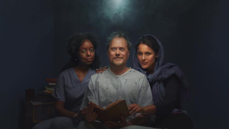 Une infirmière, un patient en jaquette et une femme portant un voile, tous trois assis sur un lit d'hôpital