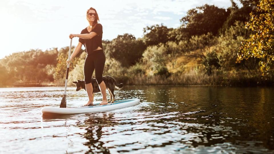 Une belle jeune femme adulte profite d'un moment paisible sur l'eau avec son paddle board et son chien de compagnie. Le soleil illumine la scène, projetant une lueur dorée.