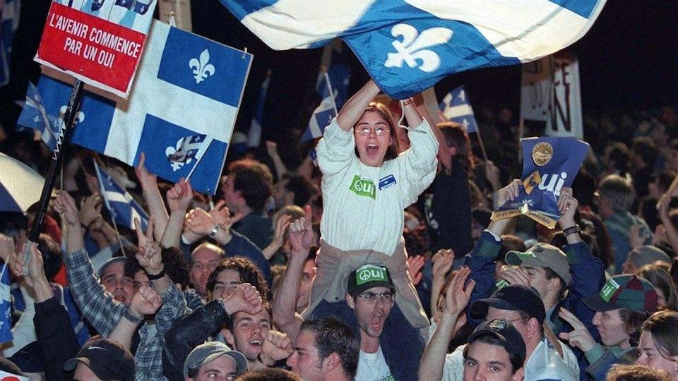 Des partisans du OUI au référendum agitent des drapeaux lors d'un rassemblement indépendantiste en 1995.