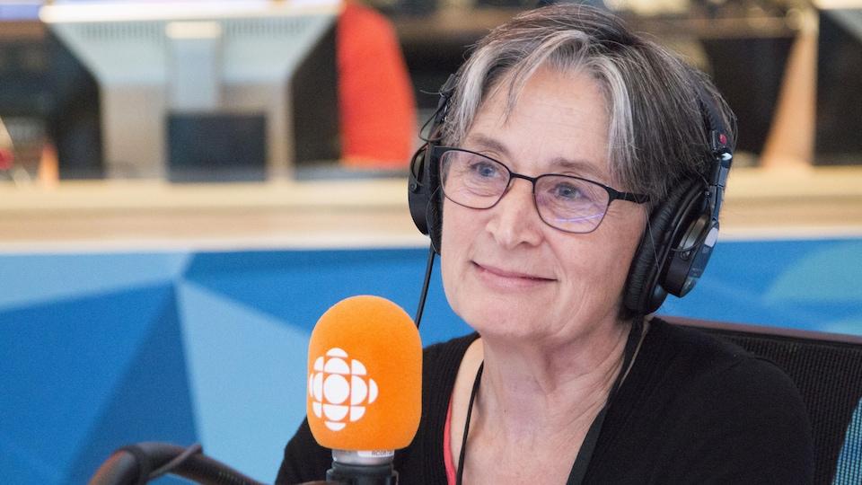 Denise Otis parle dans un micro lors d'une émission diffusée à la radio.
