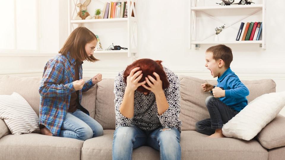Une mère à l'allure excédée se prend la tête pendant que ses enfants se disputent.