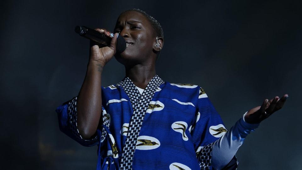 La femme est sur scène, elle tient un micro dans la main et chante.