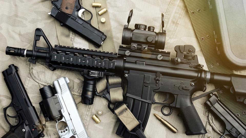 Un fusil d'assaut et deux pistolets posés sur une table.