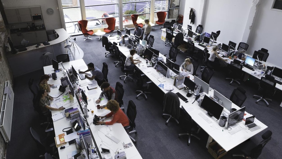 Un bureau à aire ouverte avec trois grandes tables où travaillent plusieurs personnes.