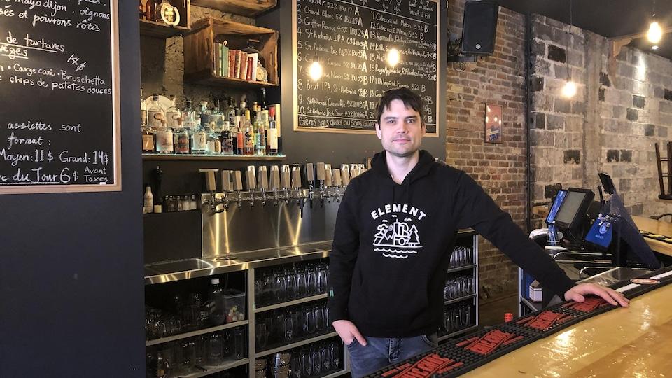 Un homme derrière un comptoir de bar.