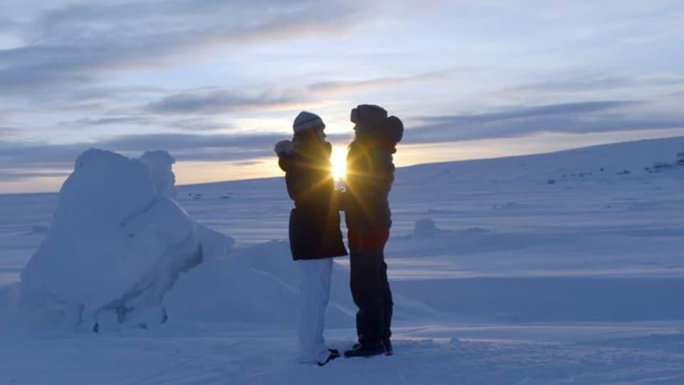 Deux femmes sur une banquise avec un coucher du soleil