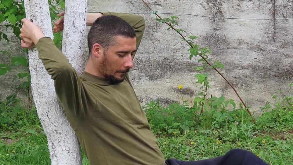 Un homme anxieux est accoté à un jeune arbre.