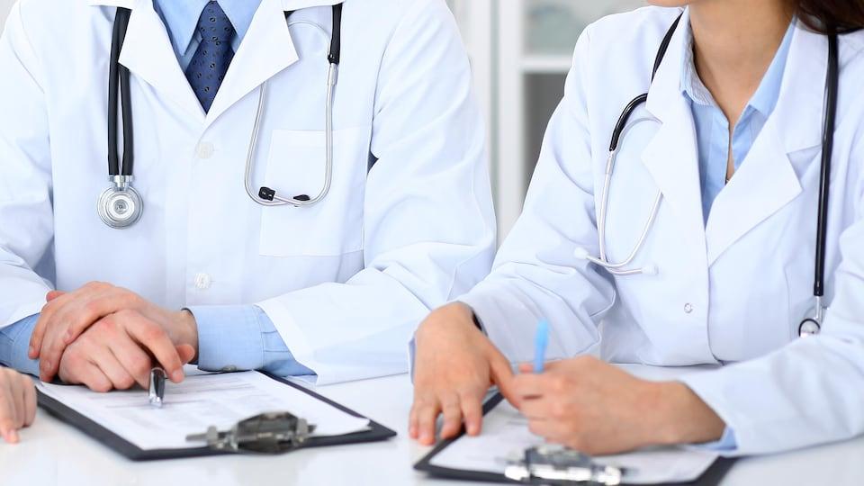 Des médecins assis autour d'une table en mode discussion.