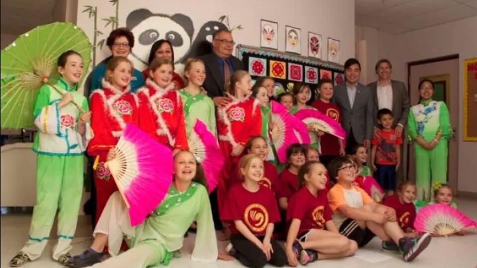Une classe avec des jeunes en costume d'origine chinoise avec leurs professeurs et directeurs