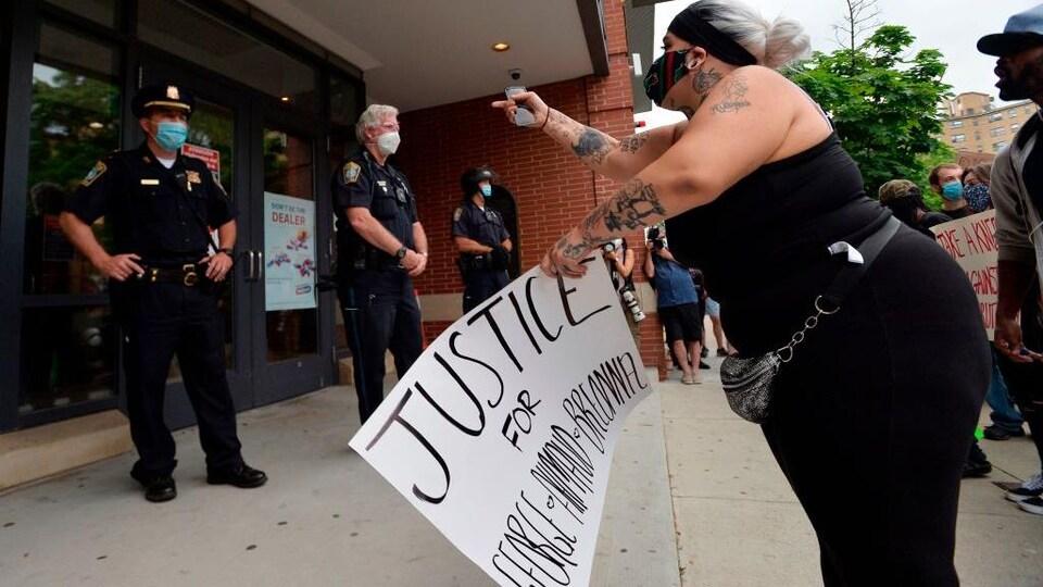 Une manifestante devant des policiers qui tient une pancarte demandant justice pour George Floyd, Ahmaud Arbery et Breonna Taylor.