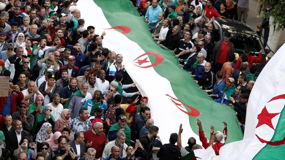 Des centaines de manifestants tiennent un long drapeau algérien dans la rue.