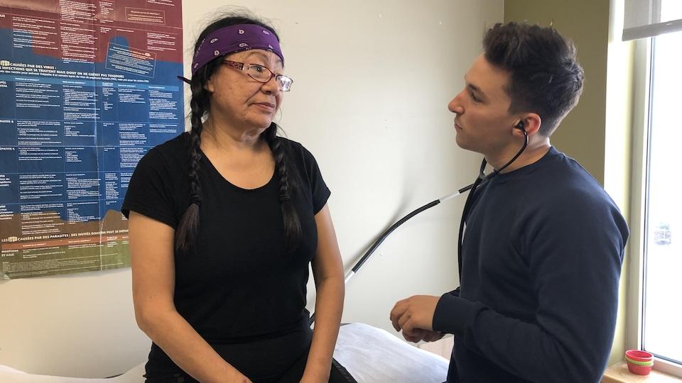 Un médecin examine une femme autochtone.