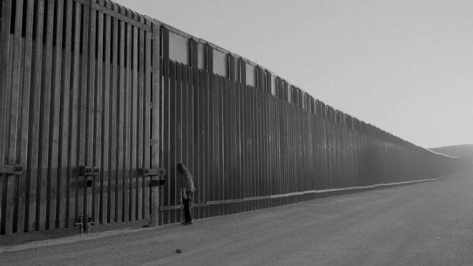 Une femme regarde à travers une immense clôture