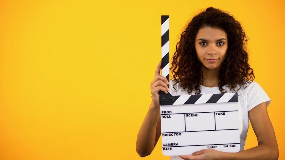 Une femme à la peau noire tient un clap de cinéma dans ses mains.