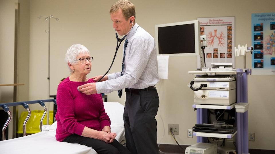 Un médecin examine une patiente avec un stéthoscope.