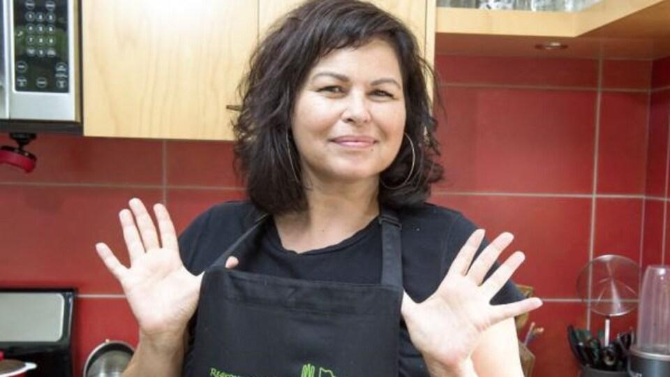 Dominique Pétin, porte-parole du Regroupement des popotes roulantes, portant un tablier, dans une cuisine