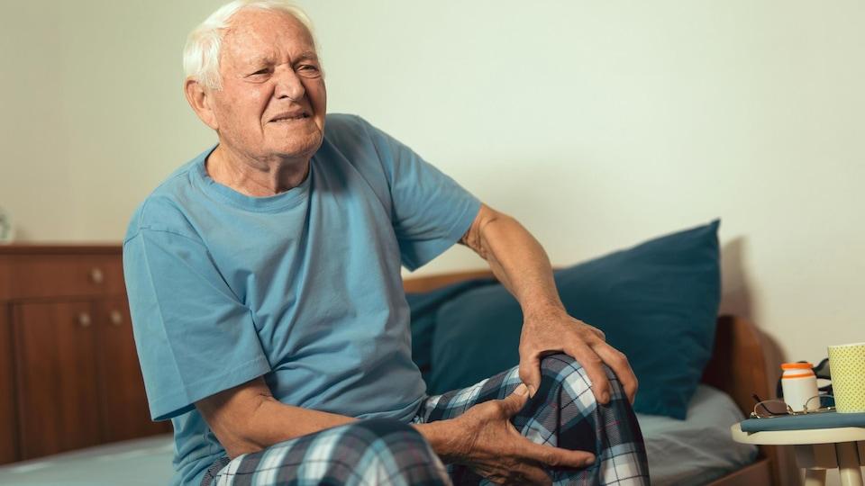 Un homme âgé grimace de douleur en se tenant le genou gauche. Il est assis sur un lit simple.