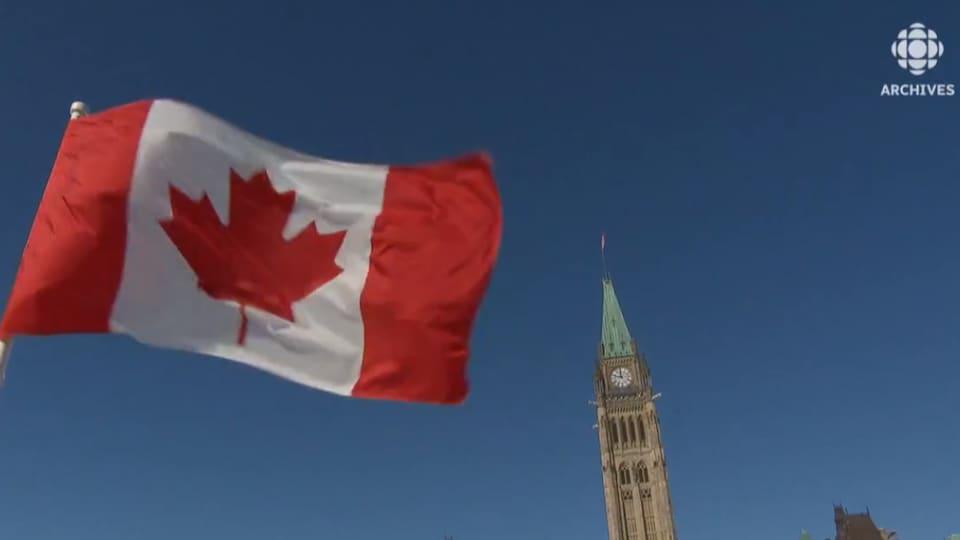 Un drapeau unifolié flotte au vent.