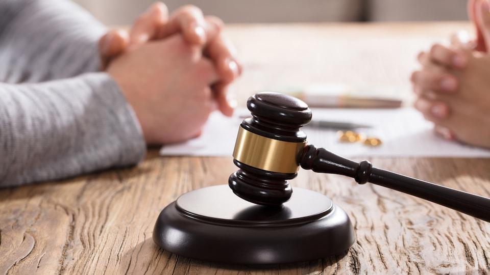 Le marteau de la justice est devant les mains d'un couple sur une table en bois.