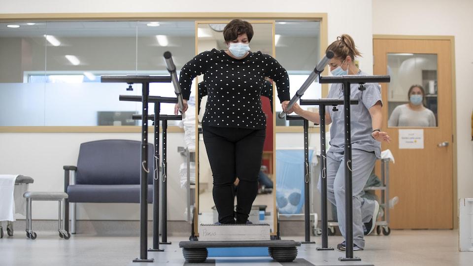 Une femme qui fait de la physiothérapie, accompagnée d'une professionnelle de santé masquée.