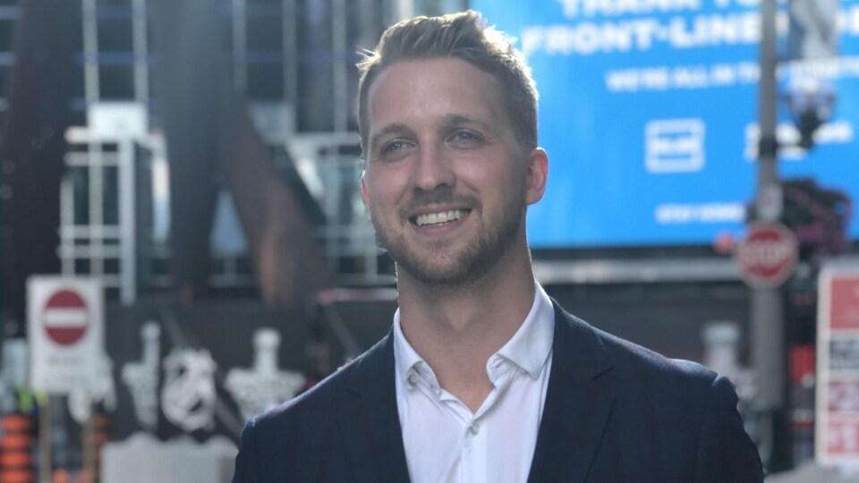 Un homme portant chemise et veston, souriant pour les caméras