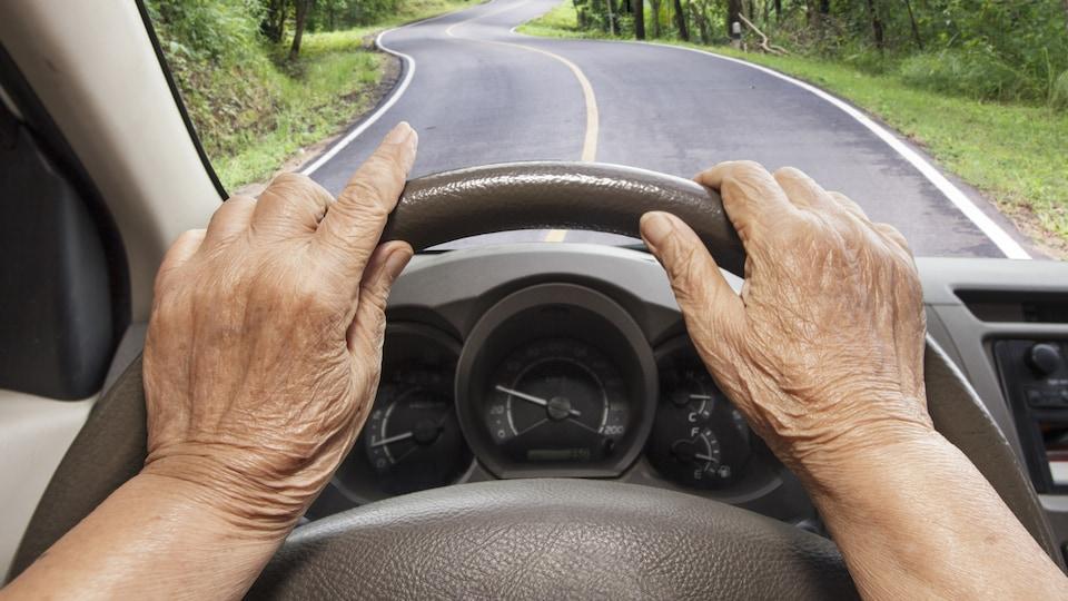 Un aîné conduisant sur une route de campagne.