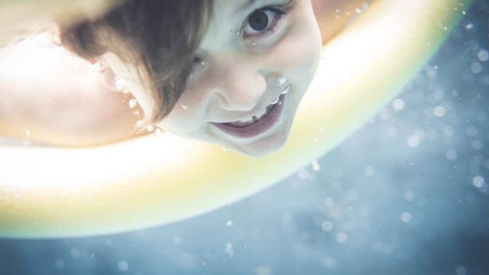 Un enfant se baigne dans une piscine.