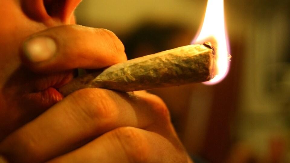Un jeune fume un joint.