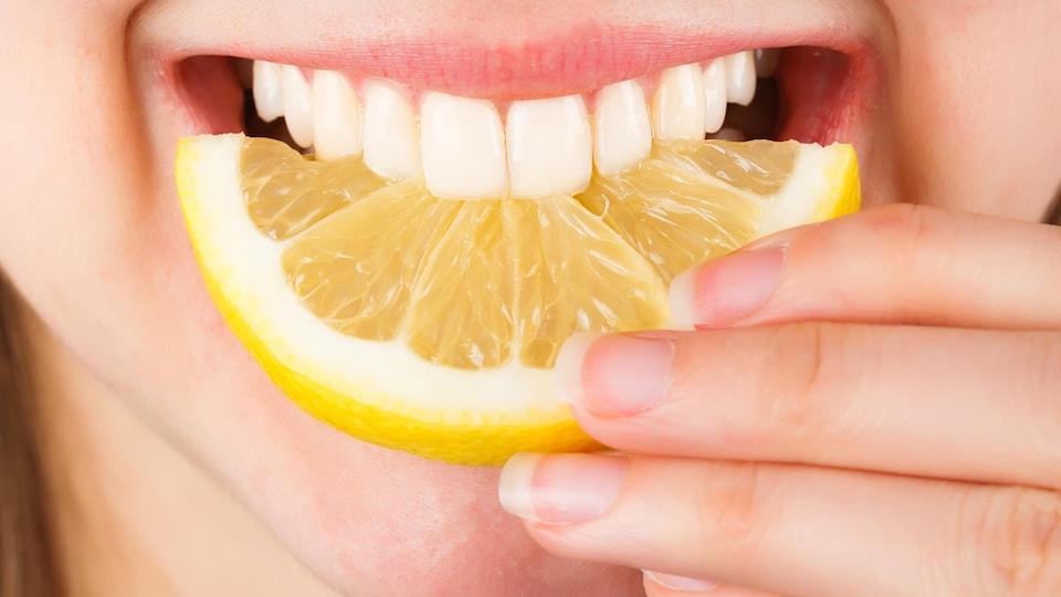 Une femme croque dans un citron.