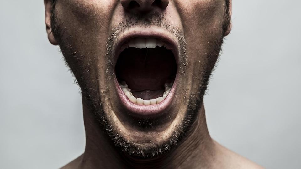 Une personne ouvre la bouche comme si elle crie.