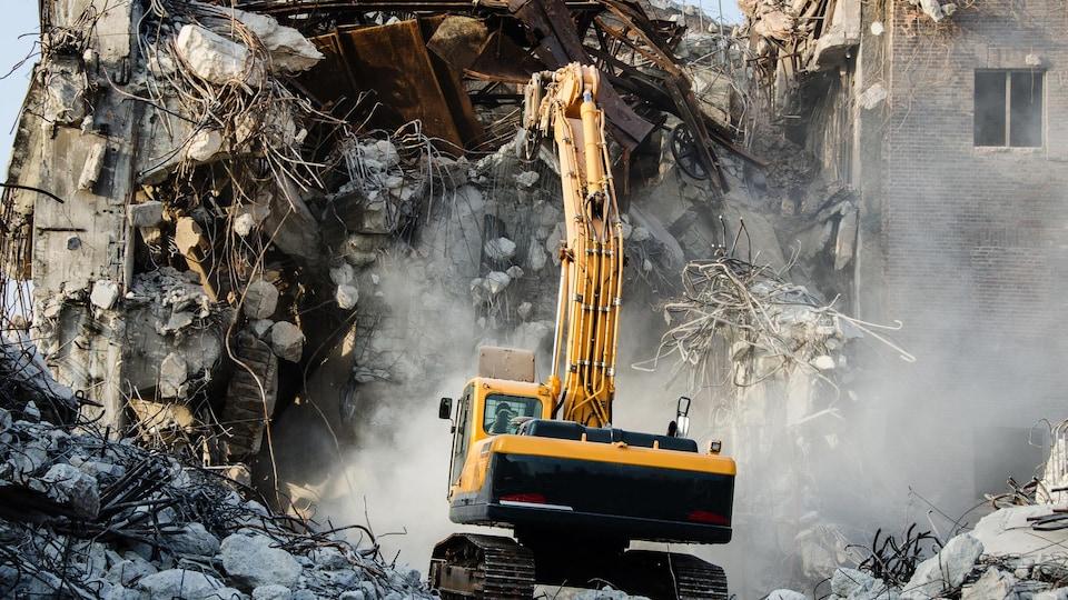Une pelle mécanique détruit un bâtiment.