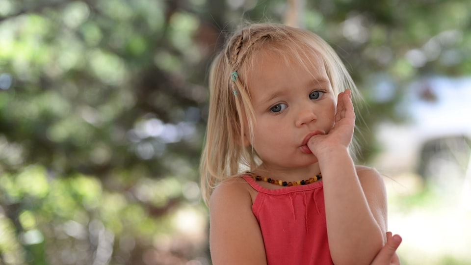 Une fillette en train se sucer son pouce.