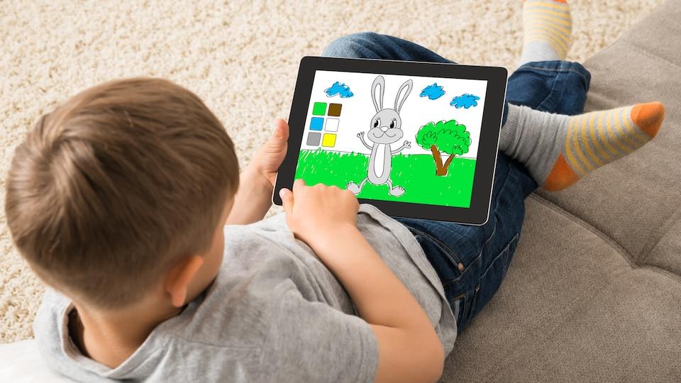 Un enfant joue avec une tablette.