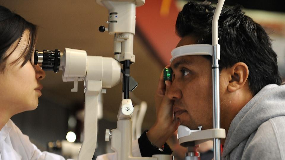 Une optométriste réalise un examen de la vue sur un homme dont le menton et le front sont appuyés contre un instrument pour stabiliser son visage.
