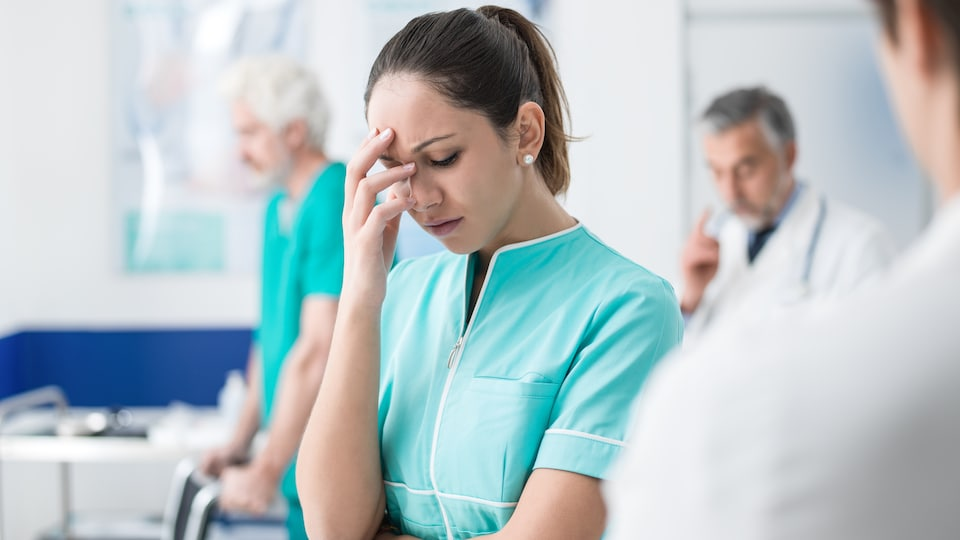 Une infirmière semble épuisée par son travail.