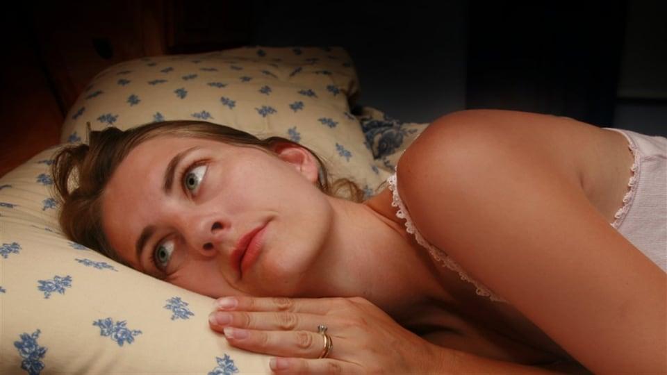 Une femme insomniaque a les yeux ouverts dans son lit.