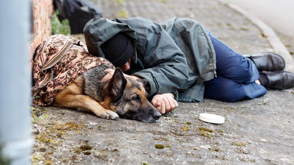 Un jeune itinérant dort sur le trottoir avec son chien.