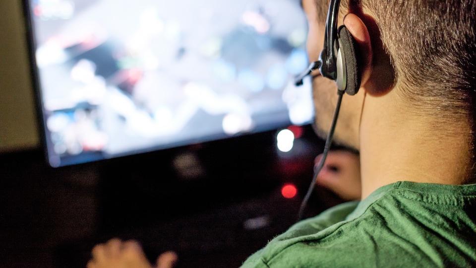 Un jeune homme joue à un jeu vidéo dans sa chambre.
