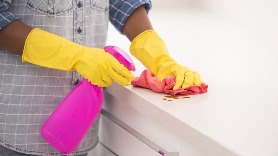 Une personne portant des gants en caoutchouc vaporise un produit nettoyant sur un comptoir.
