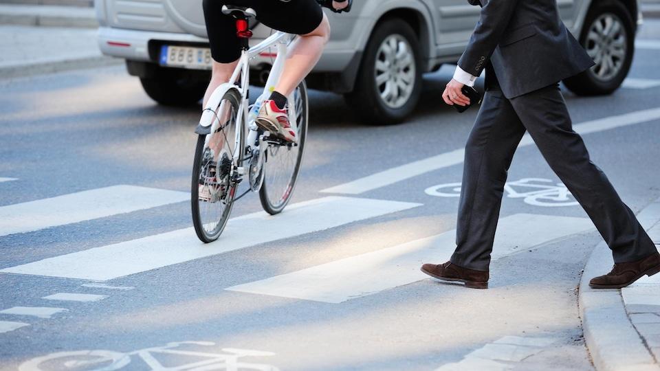 Un homme en complet s'apprête à traverser la rue.