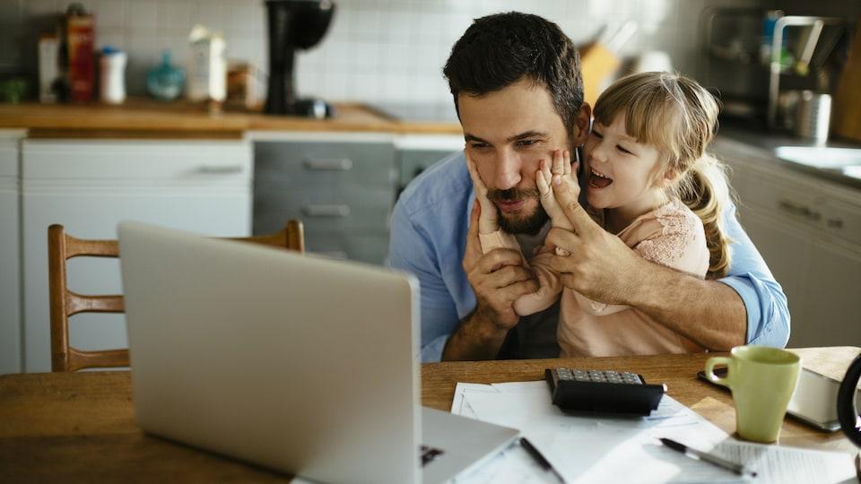 Un père et sa fille s'amusent devant un ordinateur.