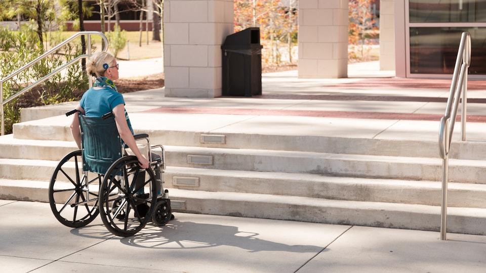 Une femme en fauteuil roulant s'arrête devant un escalier.