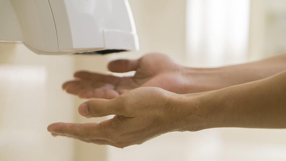 Un homme se fait sécher les mains dans une toilette publique.