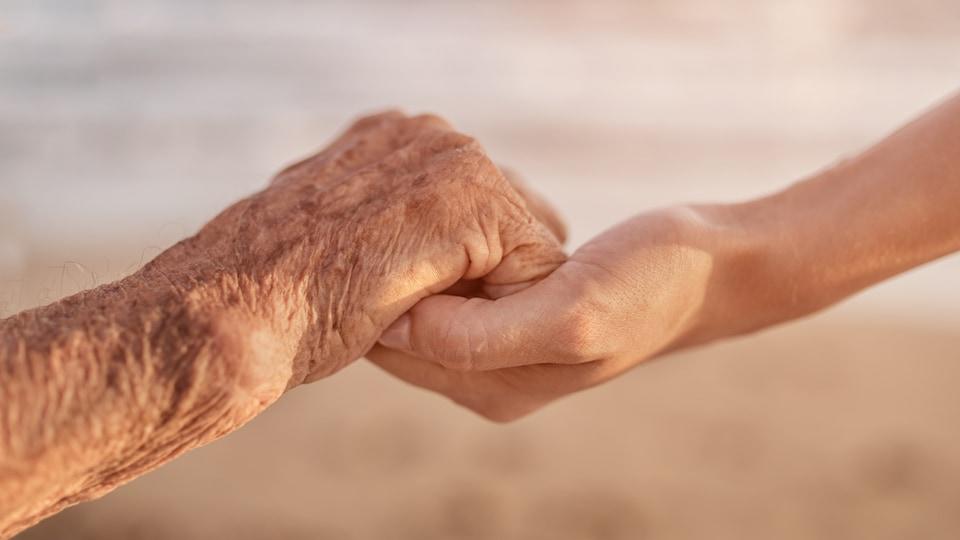 Une personne en fin de vie tient la main d'une autre personne.